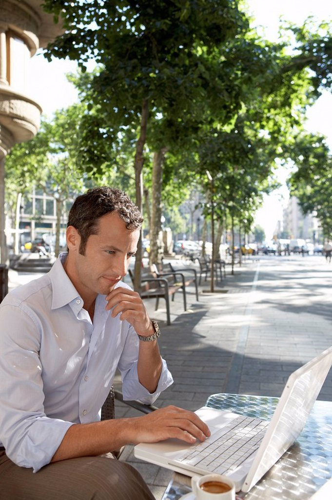 Businessman using laptop at outdoor cafe : Stock Photo