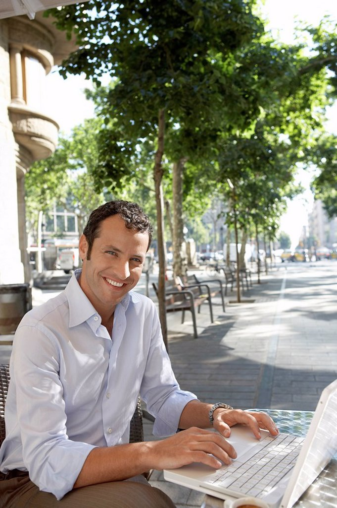 Stock Photo: 1654R-7122 Businessman using laptop at outdoor cafe