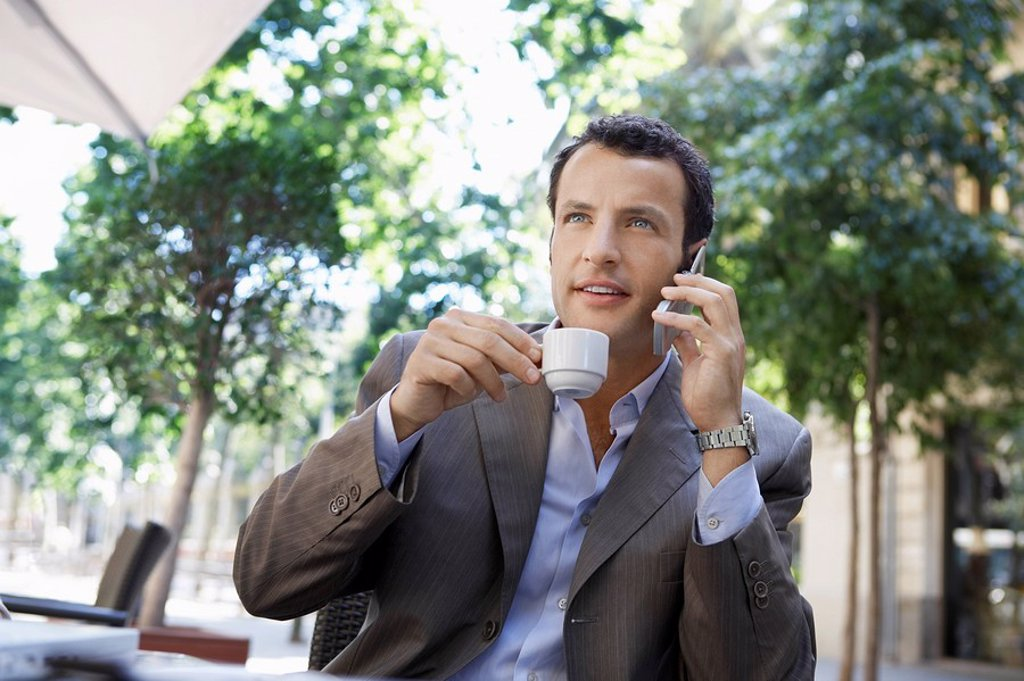 Stock Photo: 1654R-7125 Businessman using mobile phone at outdoor cafe