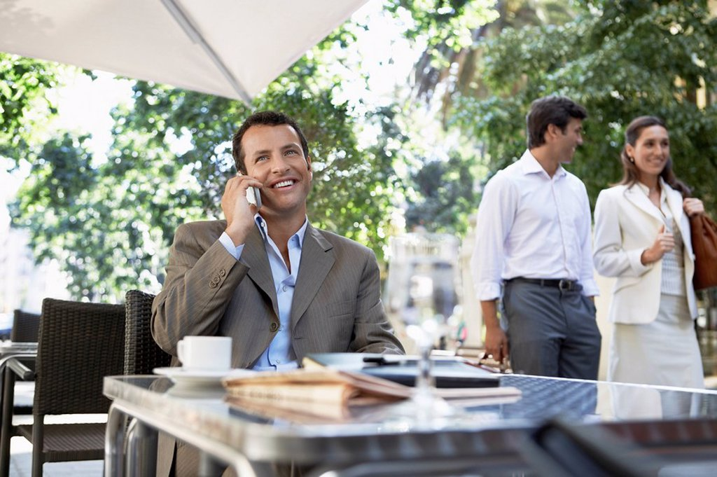Businessman using mobile phone at outdoor cafe : Stock Photo