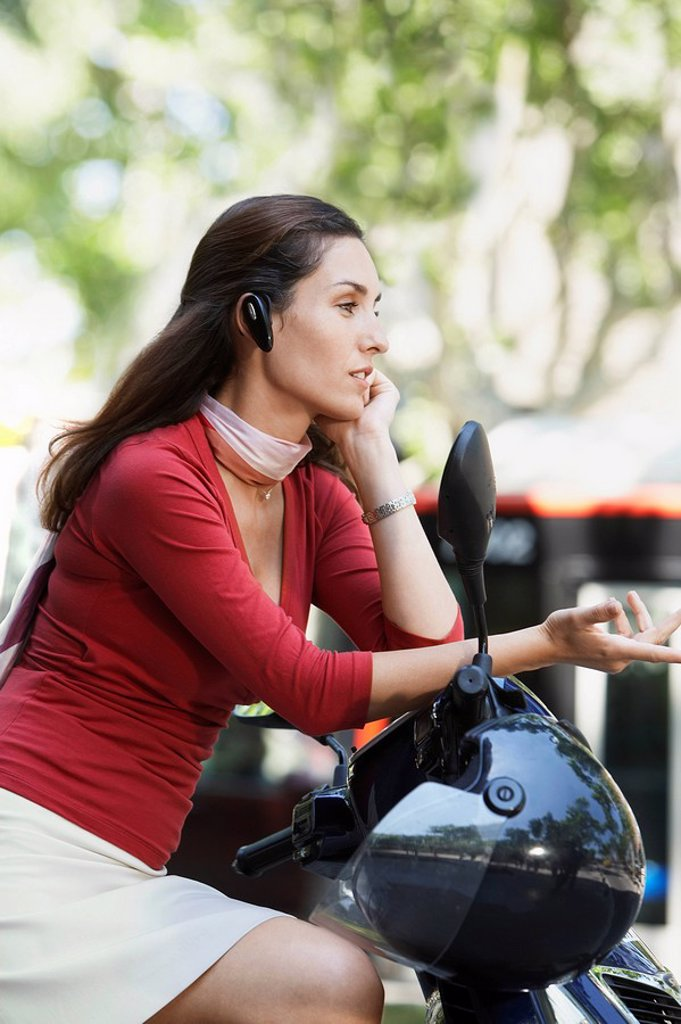 Stock Photo: 1654R-7138 Businesswoman Using Cell Phone on Moped