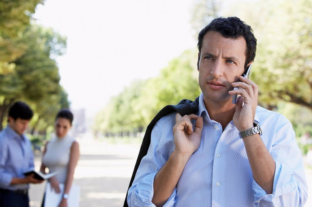 Businessman using mobile phone in park : Stock Photo