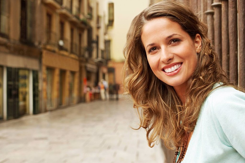 Stock Photo: 1654R-7177 Young woman standing outside buildings in street portrait.