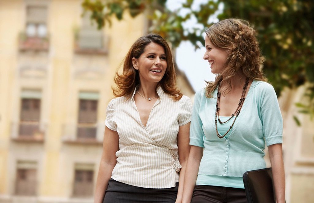 Stock Photo: 1654R-7178 Two businesswomen walking together through old town.