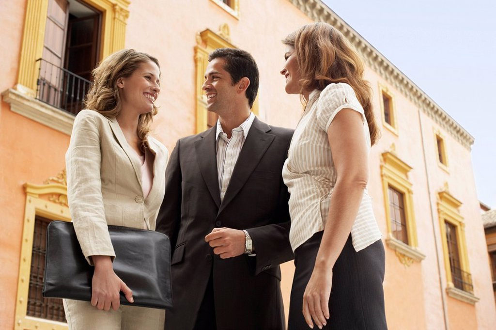 Stock Photo: 1654R-7180 Two businesswomen and one businessman standing outdoors low angle view.