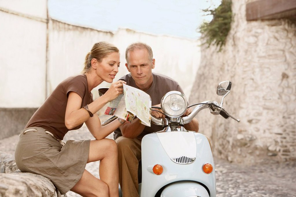 Stock Photo: 1654R-7198 Couple With Scooter Reading Map on old street in Granada Spain