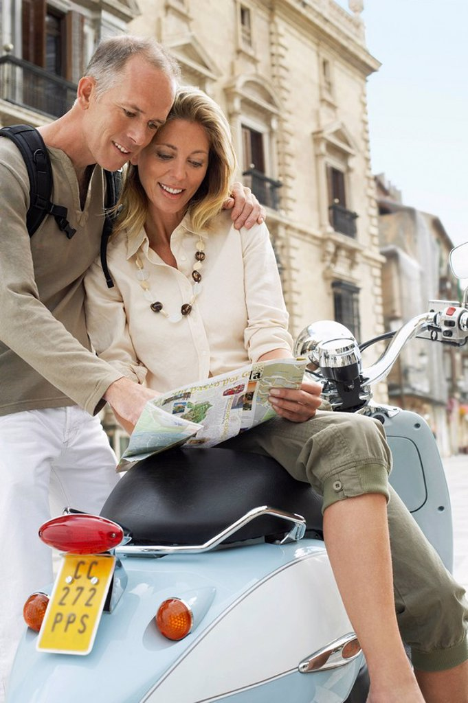 Couple With Scooter Reading Map on old street in Granada Spain : Stock Photo