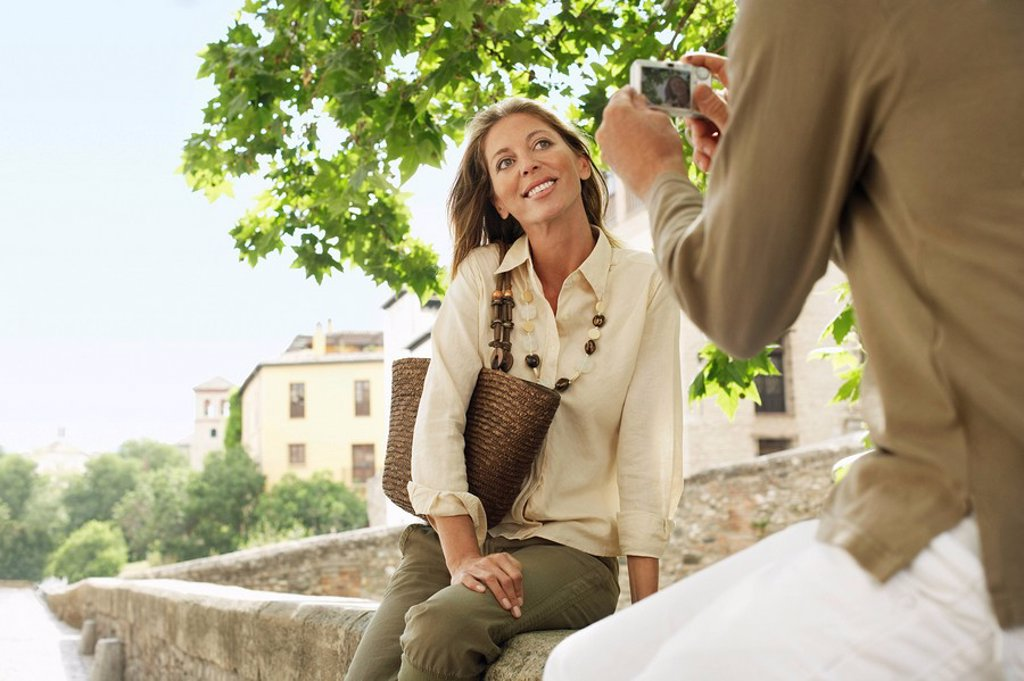 Stock Photo: 1654R-7202 Man taking picture of partner on wall in Granada Spain back view low angle view