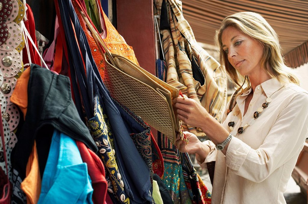 Tourist Shopping for Bags on Stall : Stock Photo