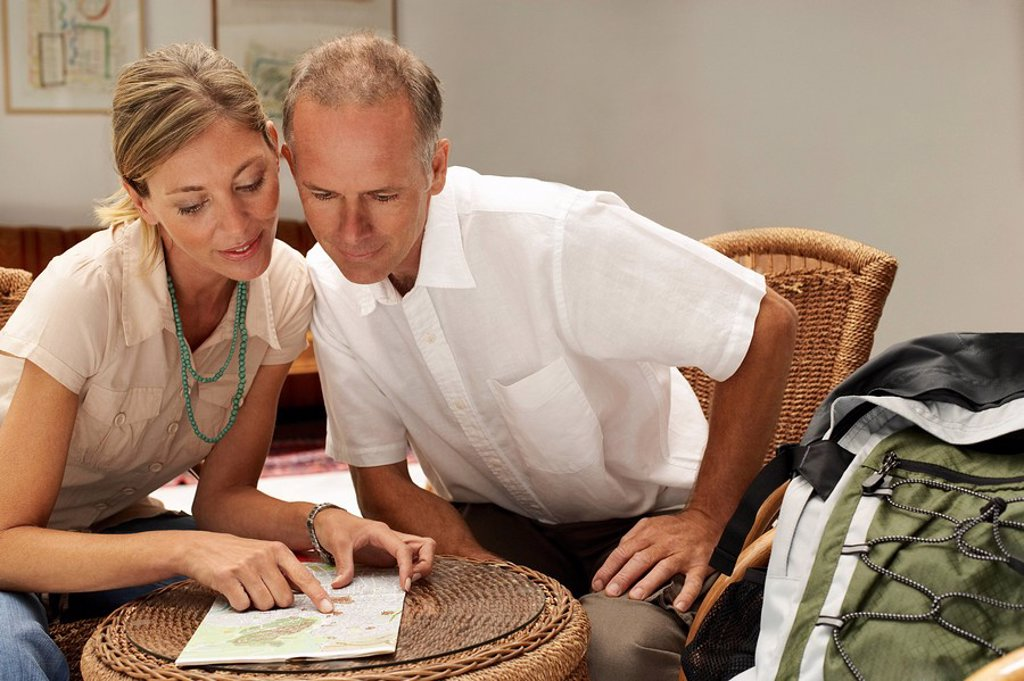 Tourist Couple in Cafe looking at map front view : Stock Photo