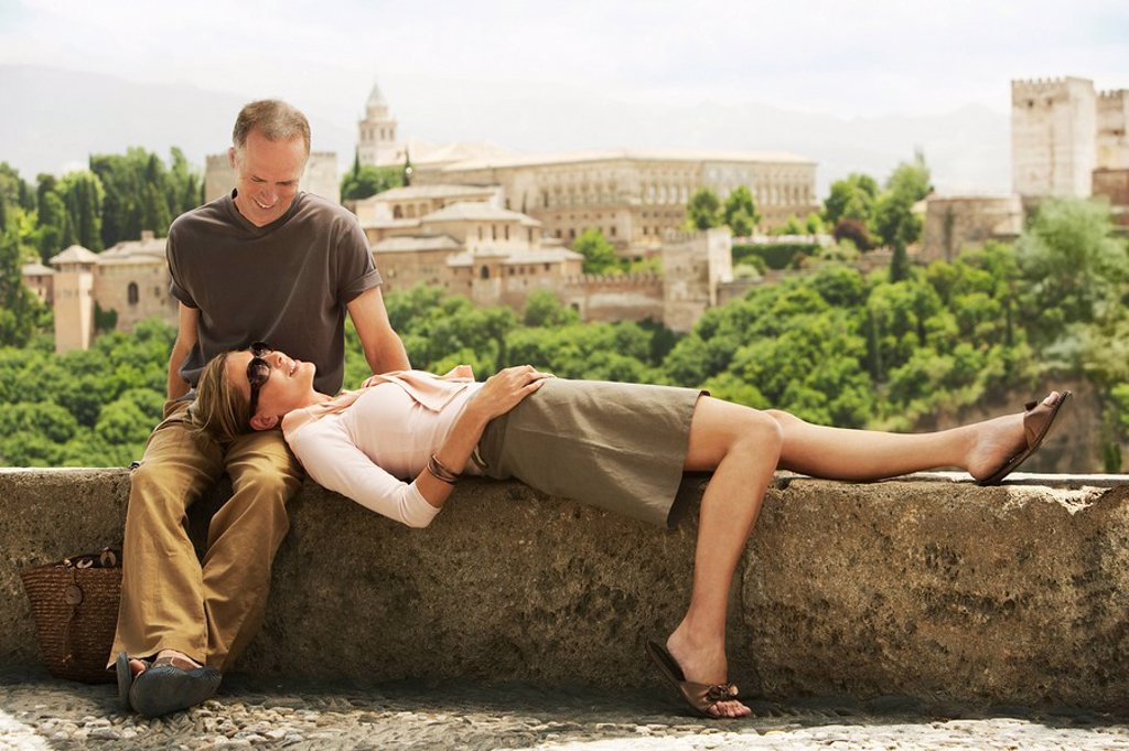 Tourist Couple Relaxing on Wall in Granada Spain : Stock Photo