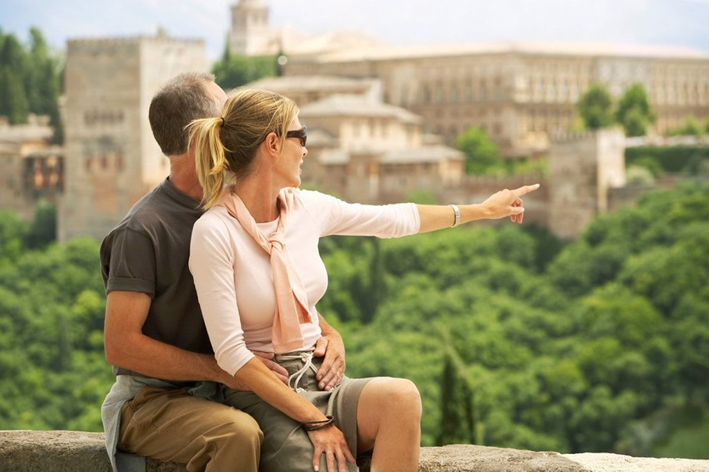 Tourist Couple sitting on Wall in Granada Spain looking and pointing at view : Stock Photo