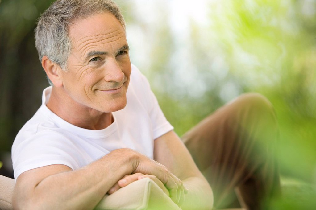 Stock Photo: 1654R-7269 Middle_aged man reclining on deck chair in garden