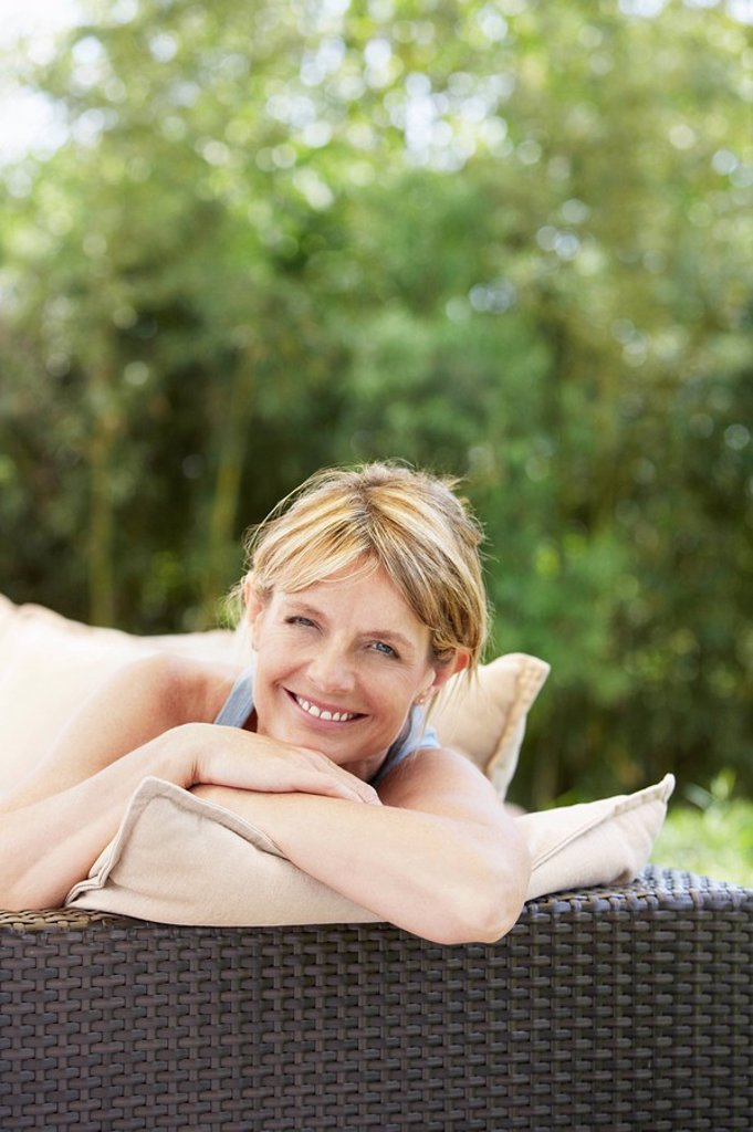 Stock Photo: 1654R-7279 Middle_aged woman sitting on sofa in garden portrait