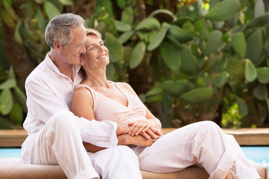 Middle_aged couple sitting outdoors cuddling by pool : Stock Photo
