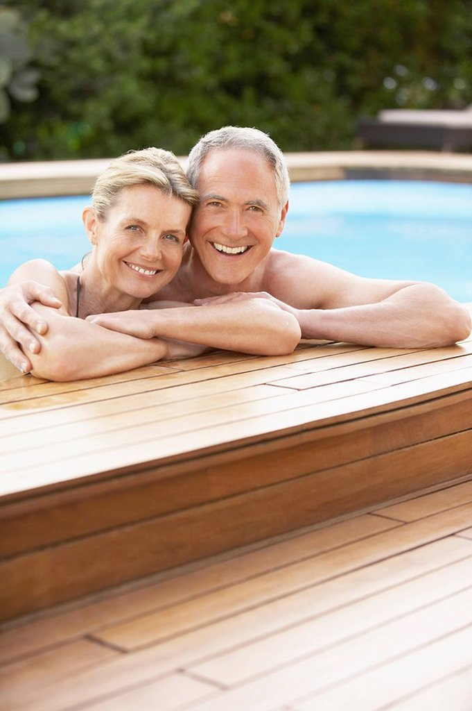 Middle_aged couple standing in pool at edge portrait : Stock Photo