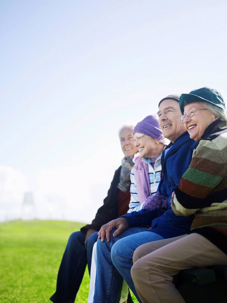 Stock Photo: 1654R-7364 Four senior friends sitting outdoors laughing