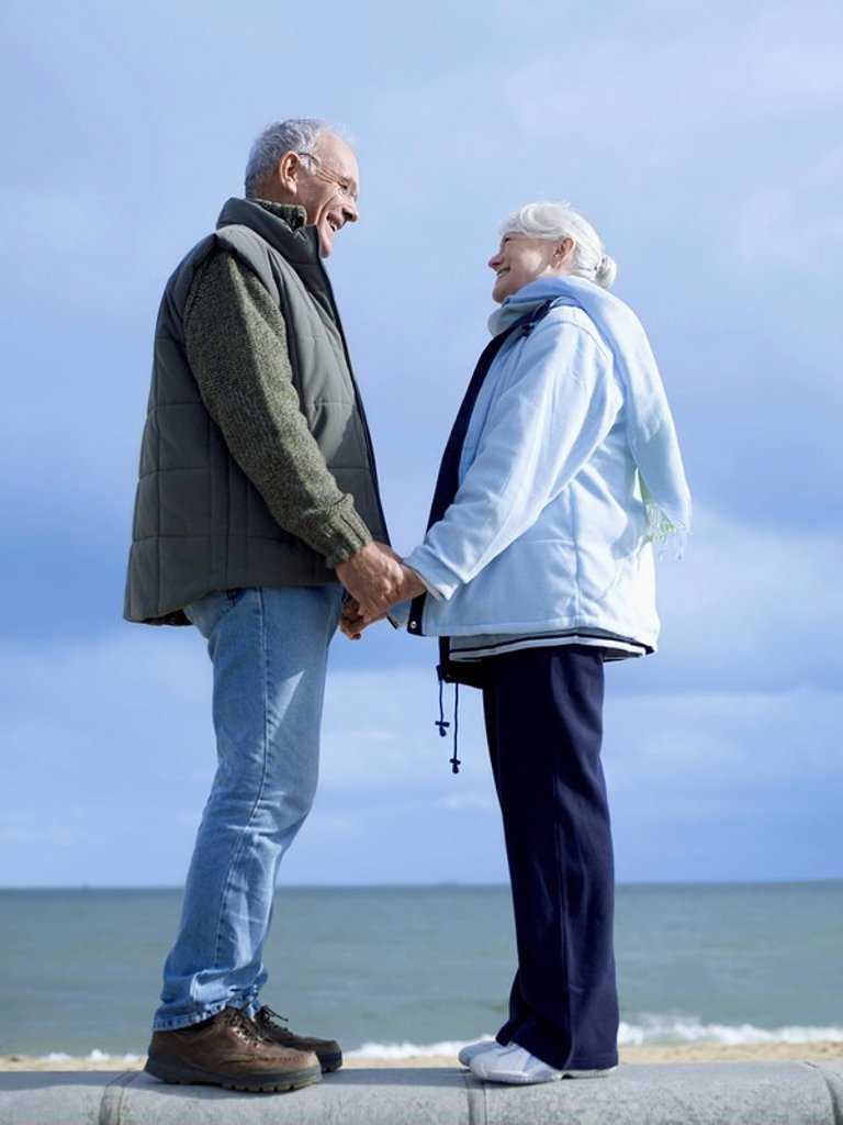 Stock Photo: 1654R-7369 Senior couple standing on wall by water holding hands