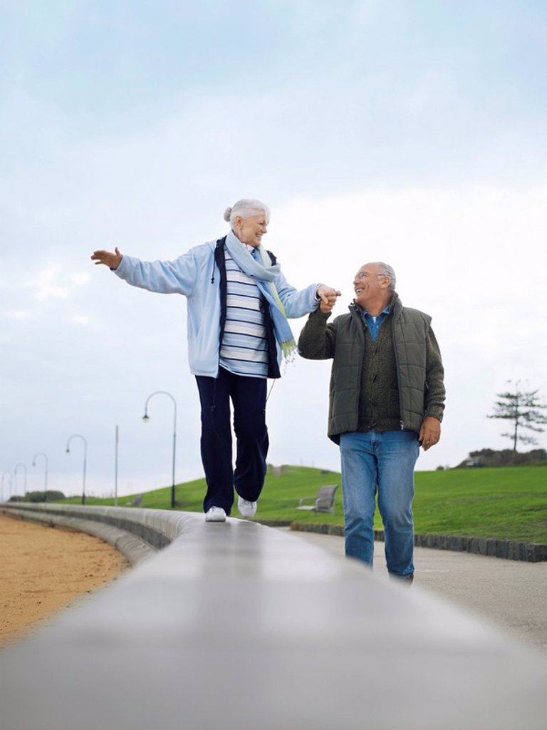 Senior couple walking on wall holding hands : Stock Photo