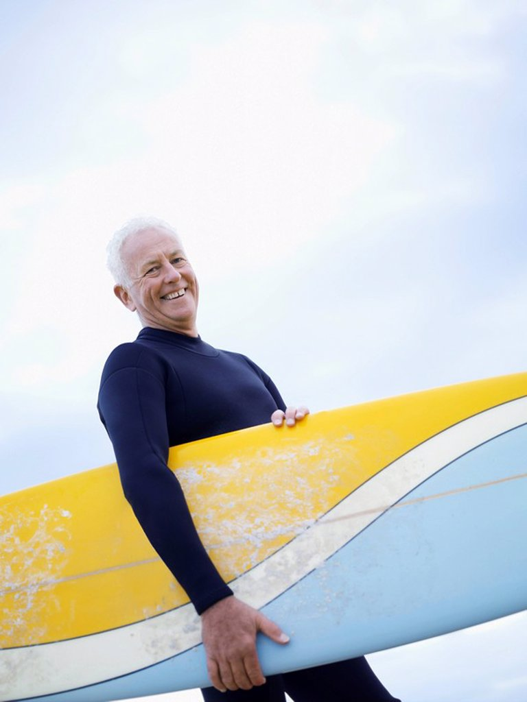 Senior man carrying surfboard smiling : Stock Photo