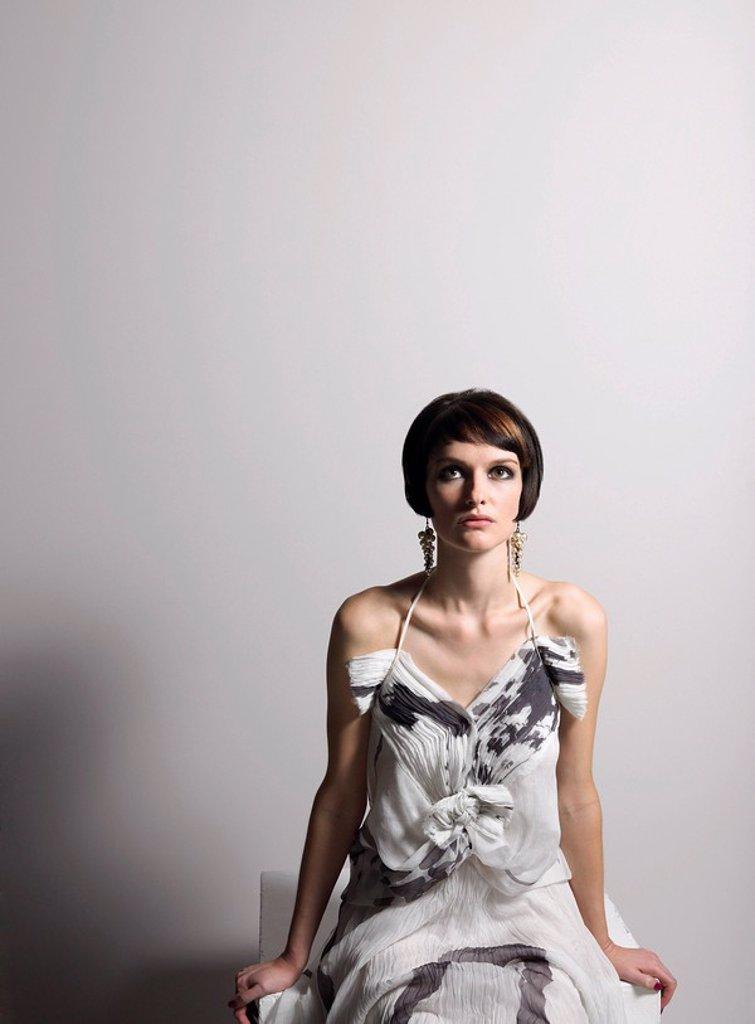 Stock Photo: 1654R-7462 Woman in dress sitting in studio
