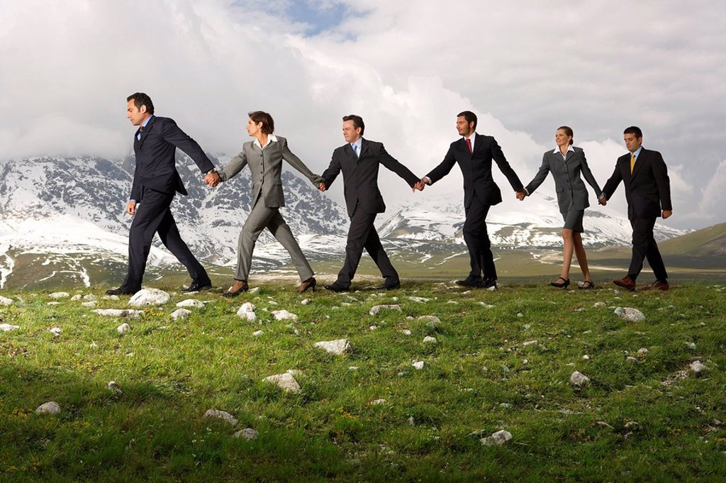 Stock Photo: 1654R-7652 Business People Holding Hands and Walking through mountains side view