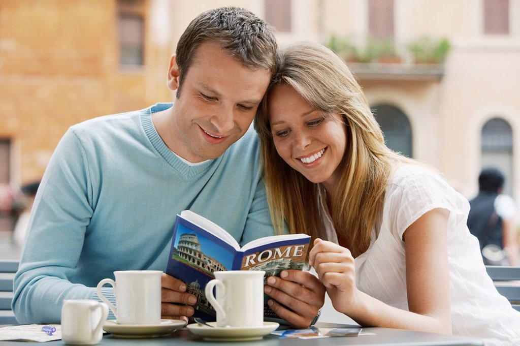 Couple at outdoor cafe looking at guidebook of Rome front view : Stock Photo