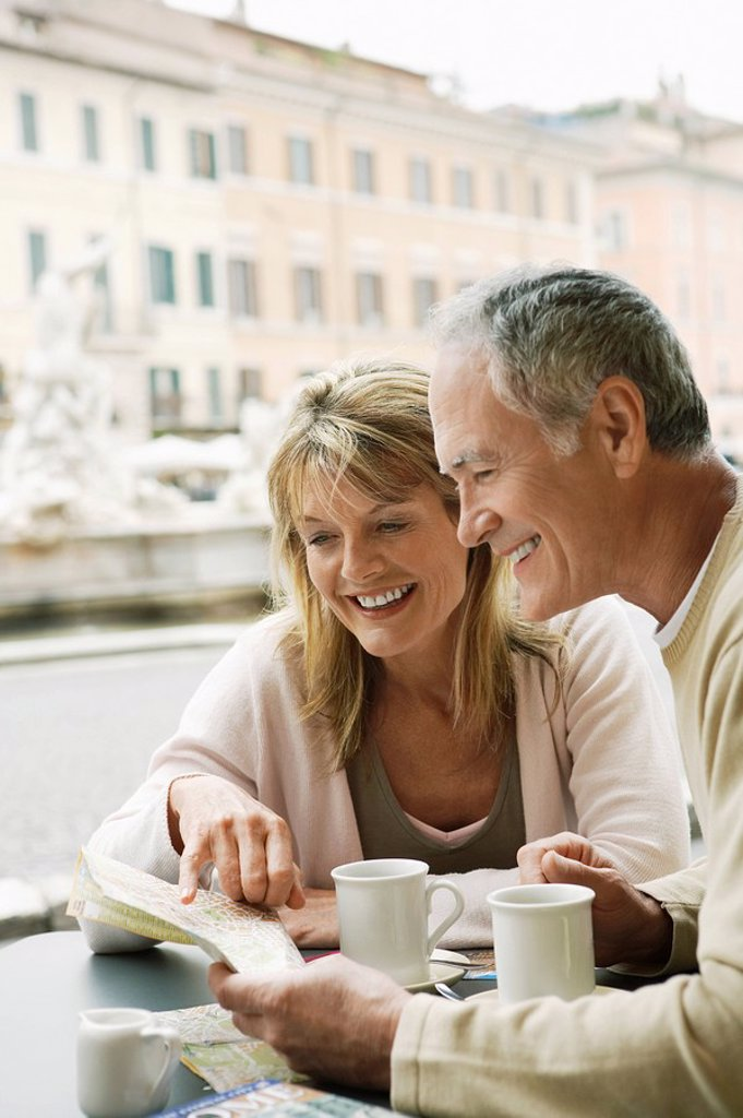 Stock Photo: 1654R-7663 Middle_aged couple at outdoor cafe in Rome looking at map head and shoulders