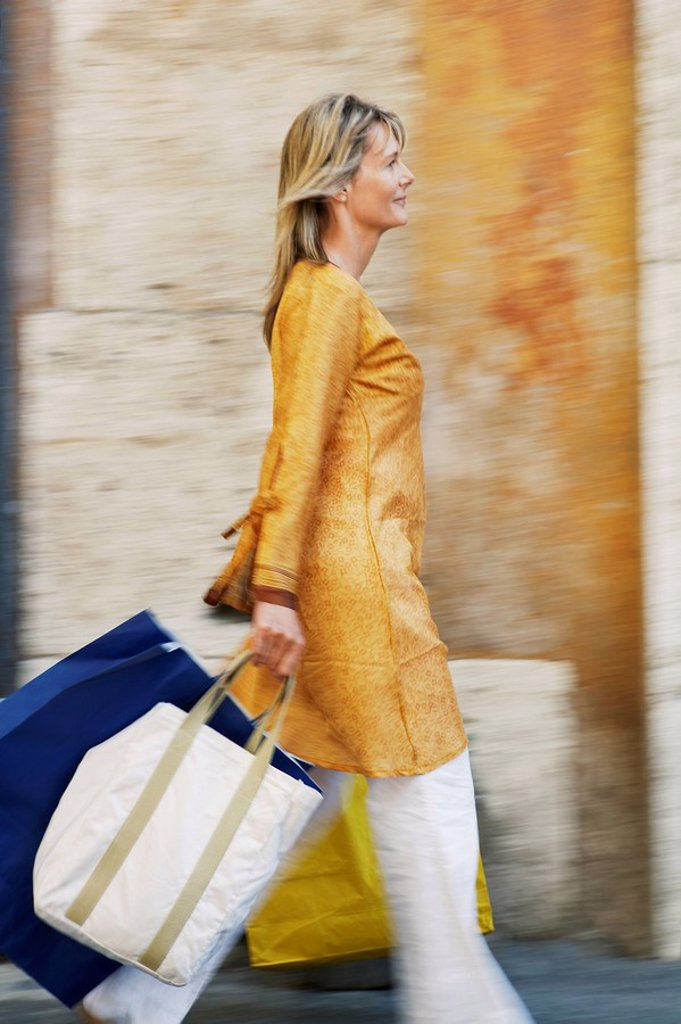 Woman Walking with Shopping Bags on street in Rome side view : Stock Photo