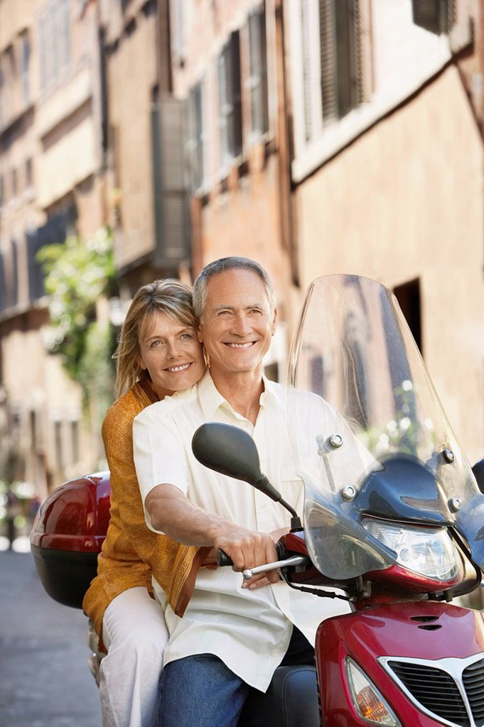 Stock Photo: 1654R-7677 Middle_aged couple on scooter on street in Rome Italy portrait