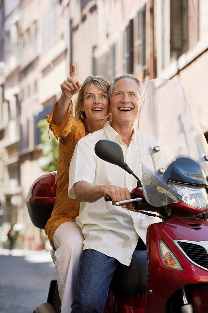 Middle_aged couple sightseeing on scooter in Rome Italy : Stock Photo