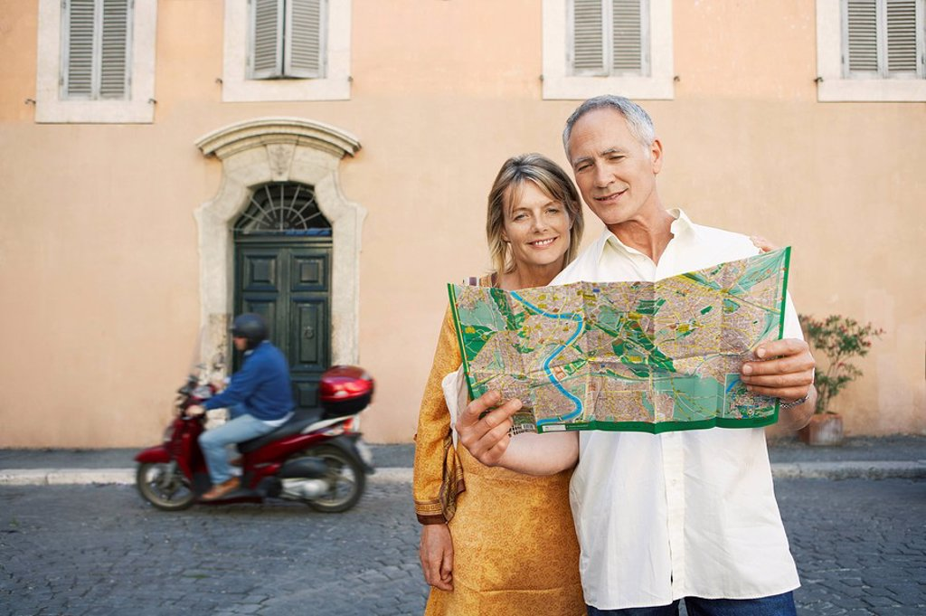 Couple on street looking at map in Rome Italy front view : Stock Photo