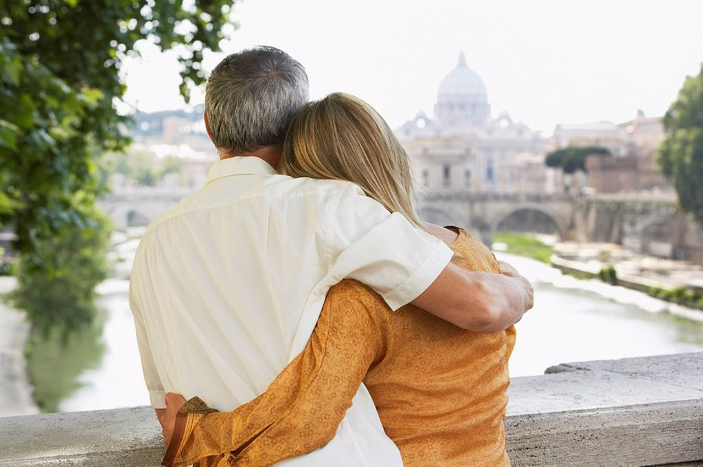 Couple on bridge in Rome Italy looking at view of cathedral back view : Stock Photo