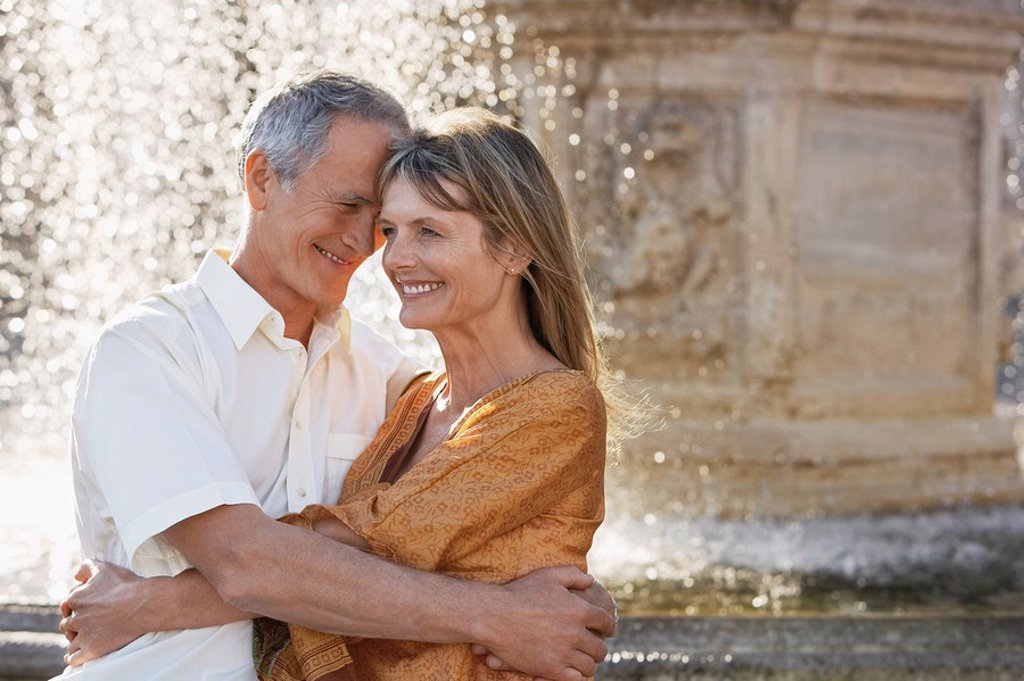 Stock Photo: 1654R-7688 Middle_aged couple hugging by fountain Rome Italy close up