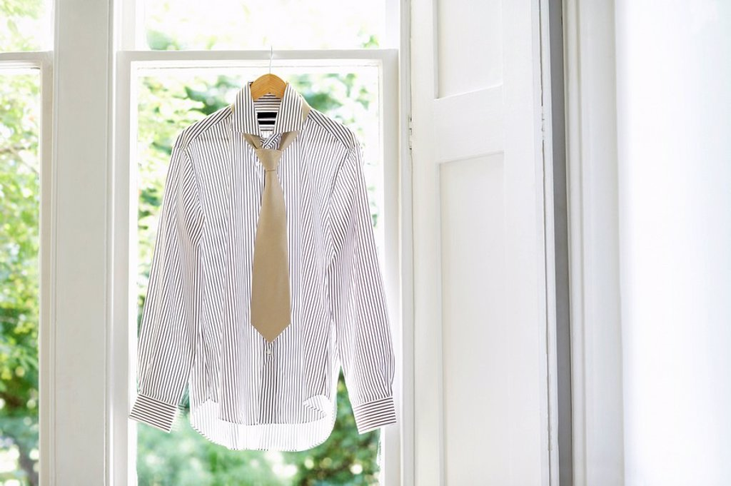 Dress shirt and tie on hanger in domestic window : Stock Photo