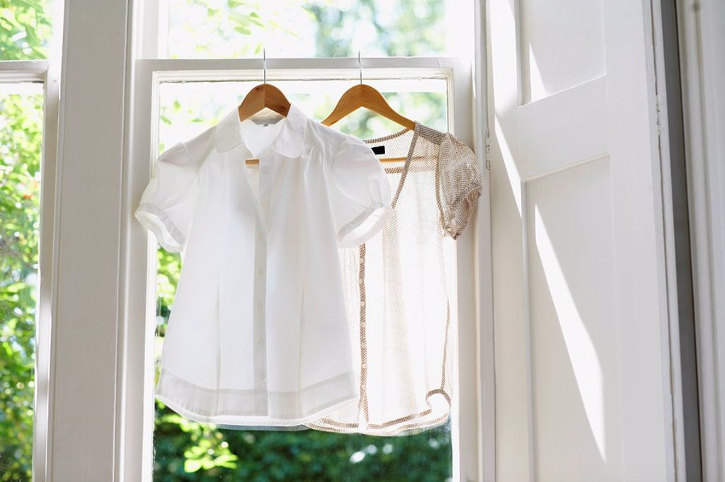 Two blouses on Hangers in domestic window : Stock Photo