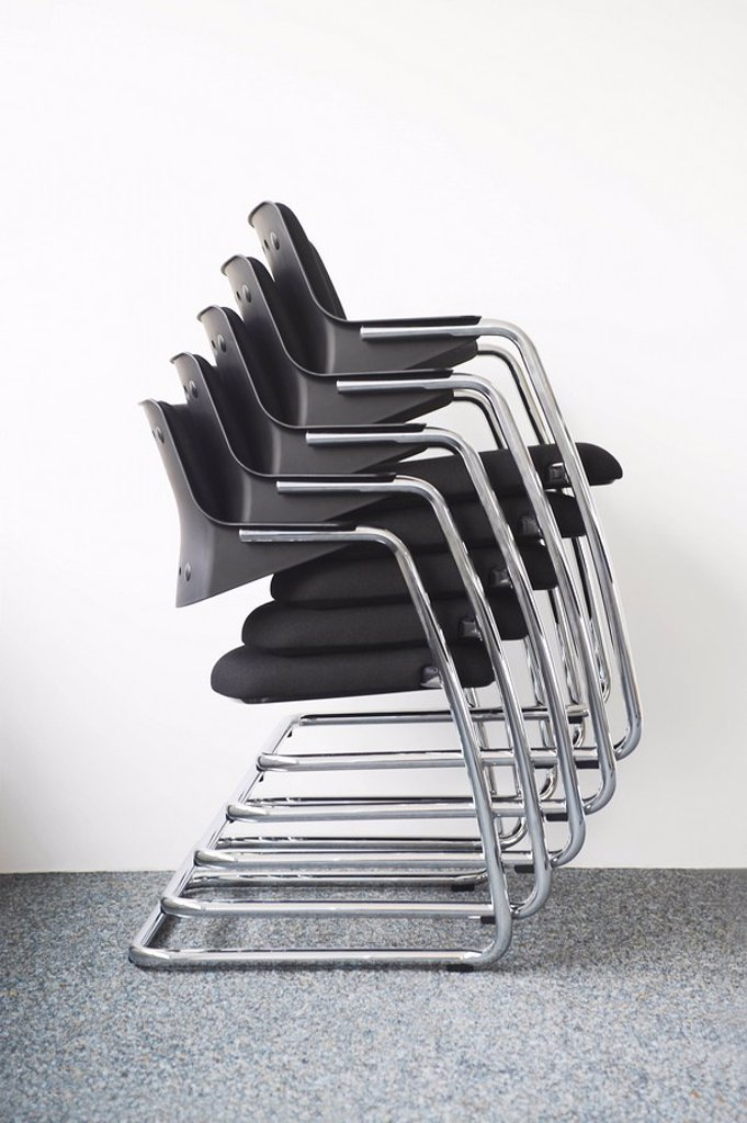 Stock Photo: 1654R-7945 Stack of office chairs against wall