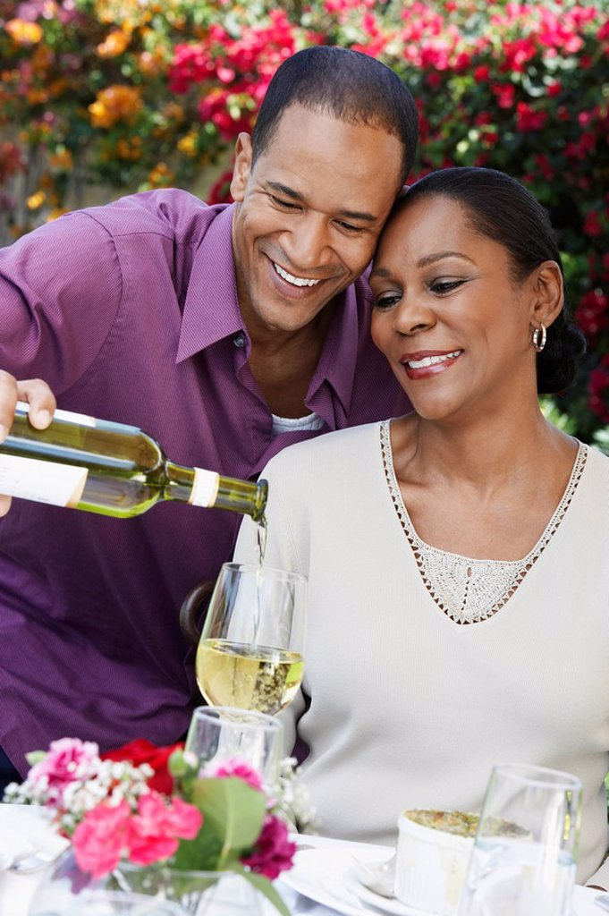 Middle aged couple sharing wine at outdoor table : Stock Photo