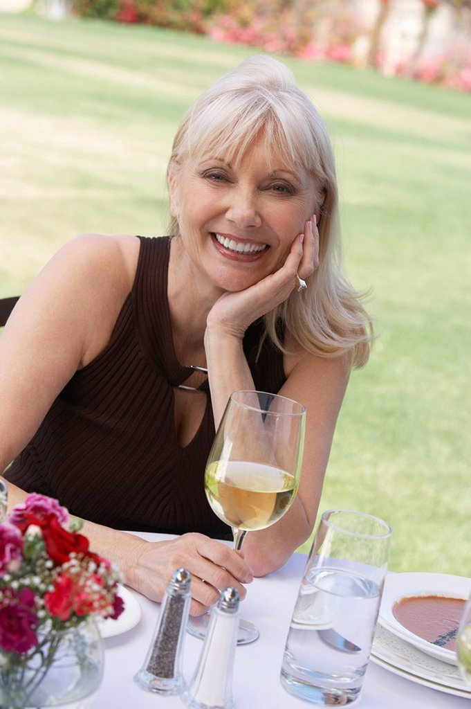 Stock Photo: 1654R-8075 Mature elegant woman sitting at table outdoors
