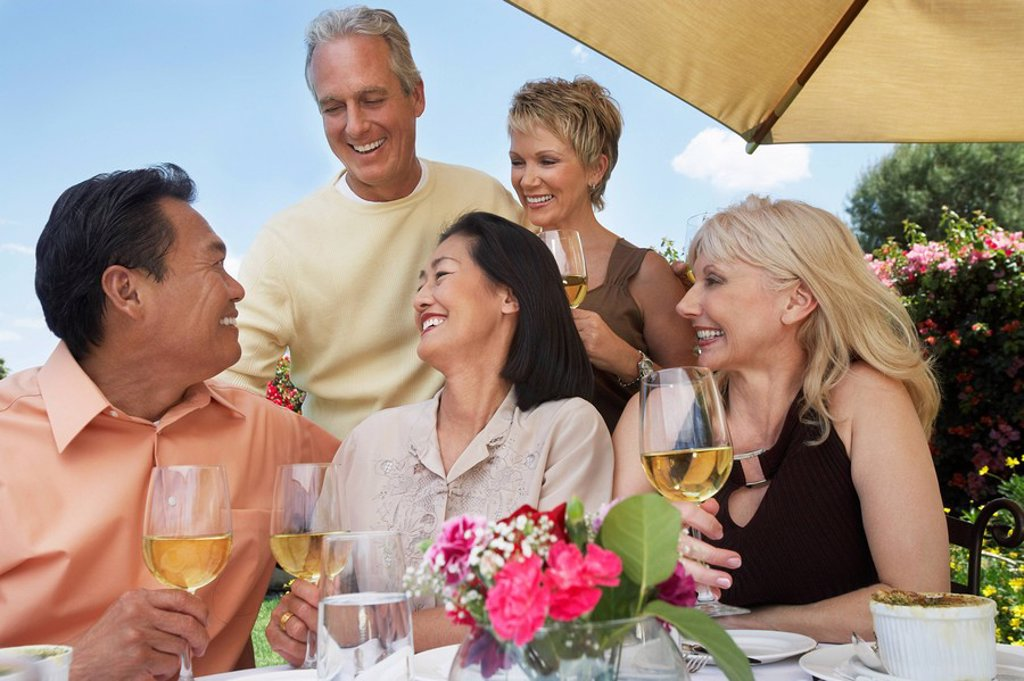 Five friends at table drinking wine at garden party : Stock Photo