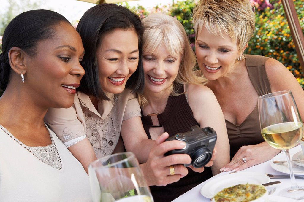 Four elegant women at garden party looking at photos on digital camera : Stock Photo