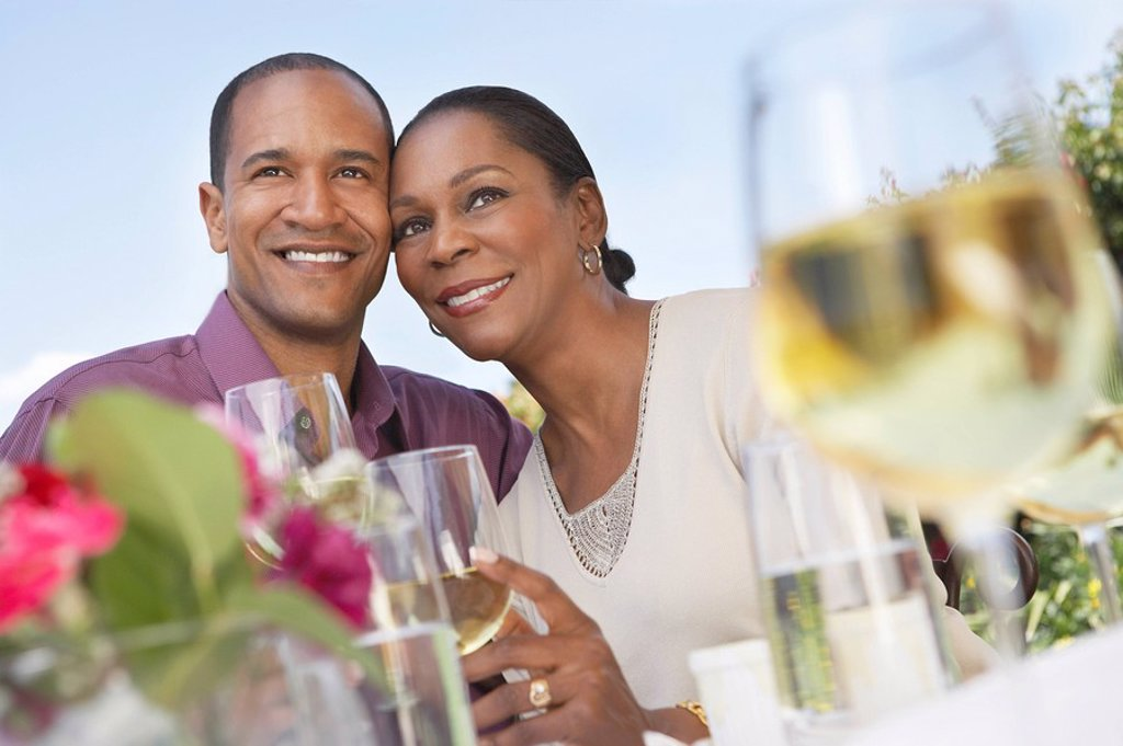 Stock Photo: 1654R-8098 Elegant couple cheek to cheek holding wine glasses at garden party table