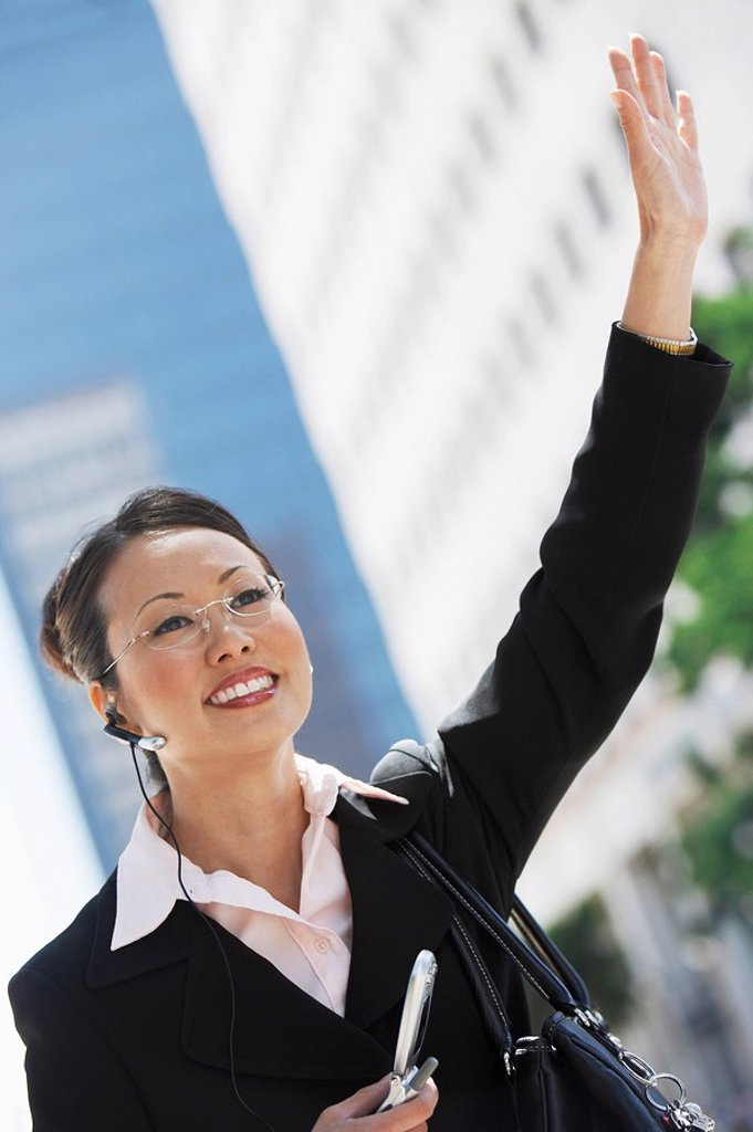 Stock Photo: 1654R-8111 Businesswoman Hailing Cab using Cell Phone with hands free