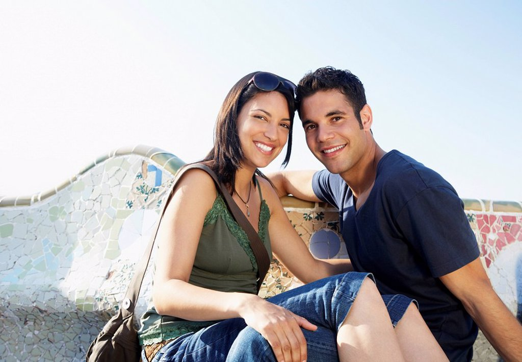 Young couple sitting on stone bench portrait : Stock Photo