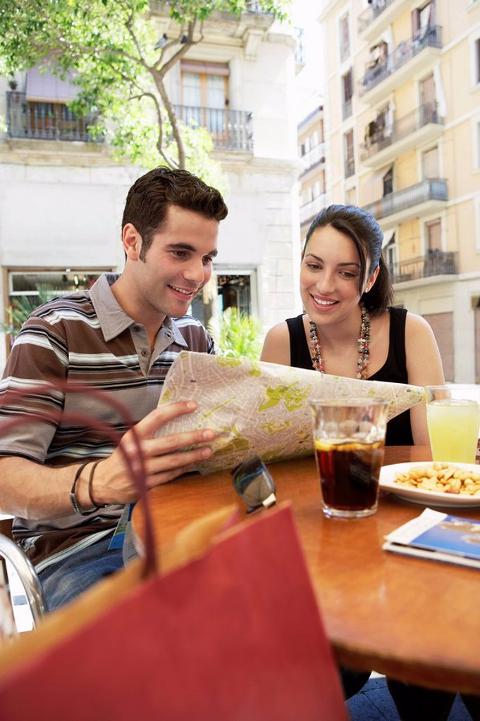 Stock Photo: 1654R-8230 Young couple at cafe reading map together portrait