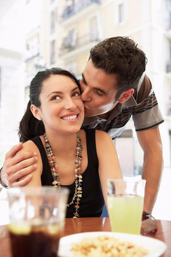 Young couple at sidewalk cafe man kissing woman portrait : Stock Photo