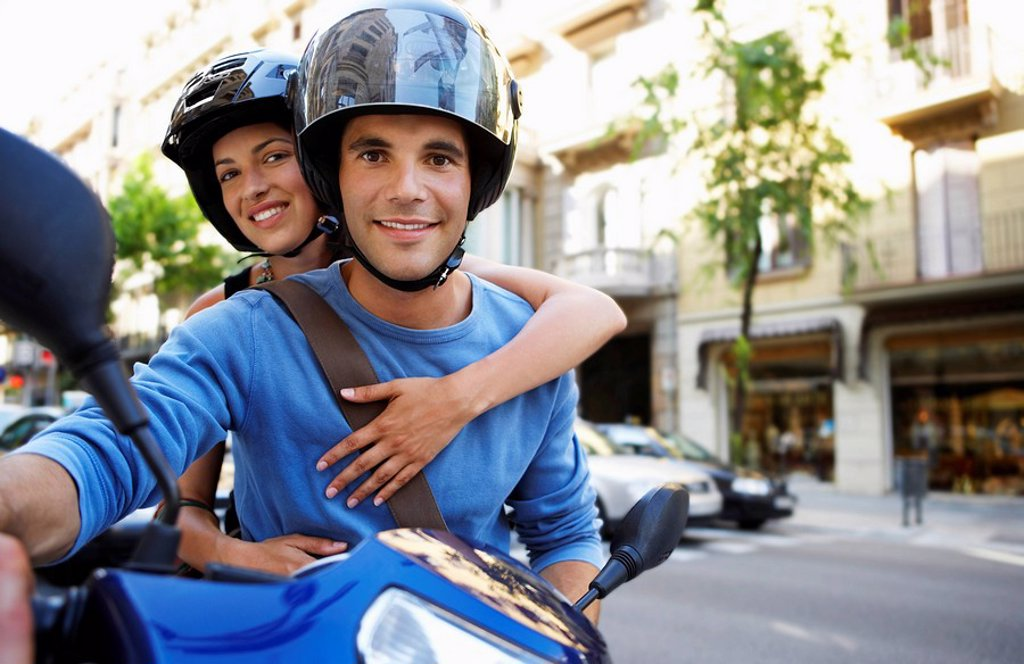 Stock Photo: 1654R-8239 Young couple on motor scooter portrait