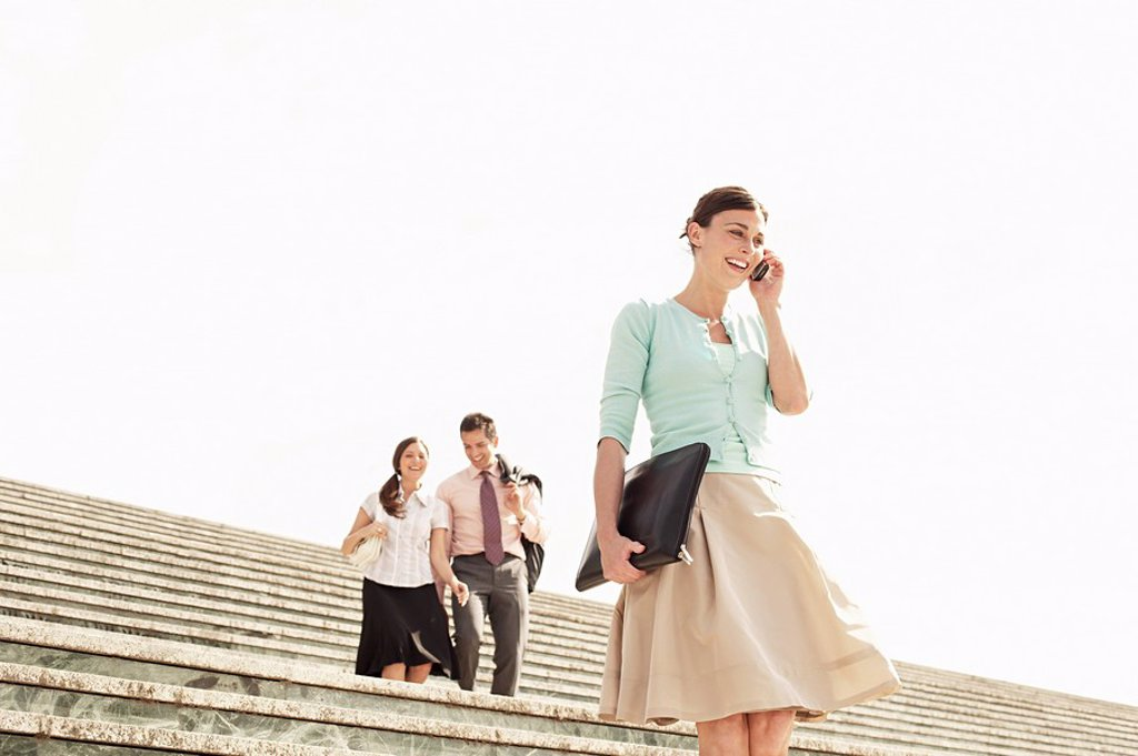 Three office workers walking down steps woman in foreground using mobile phone low angle view. : Stock Photo