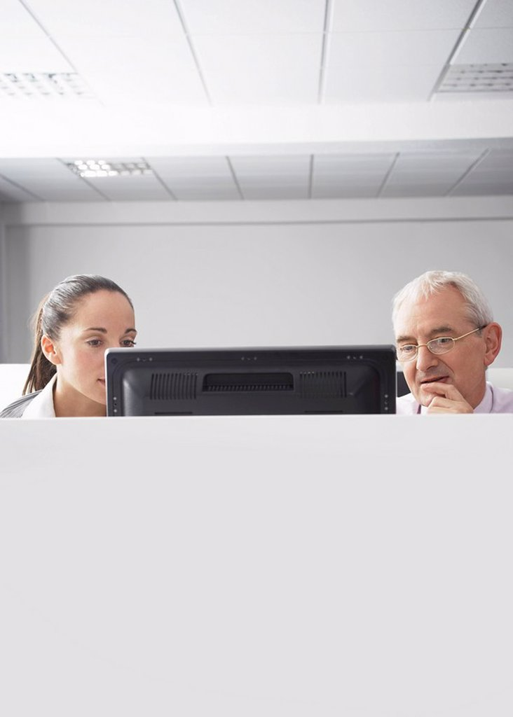 Two office workers looking at computer in office cubicle : Stock Photo