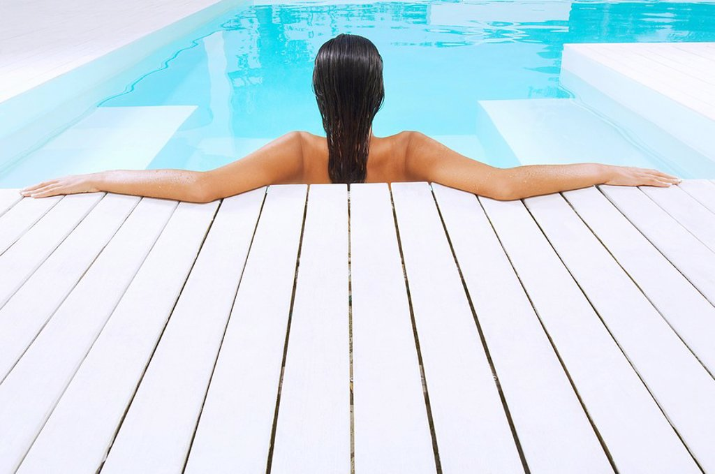 Stock Photo: 1654R-8349 Young Woman in Swimming Pool resting on poolside back view